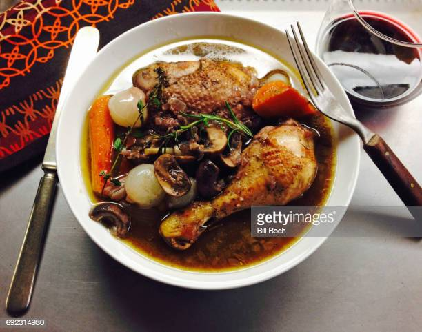Chicken coq au vin in a bowl with carrots, mushrooms, onions, herbs and a glass of red wine