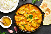 Indian chicken curry on black stone background. Top view, flat lay
