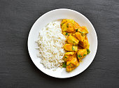 Chicken curry with rice on plate over black stone background. Top view, flat lay