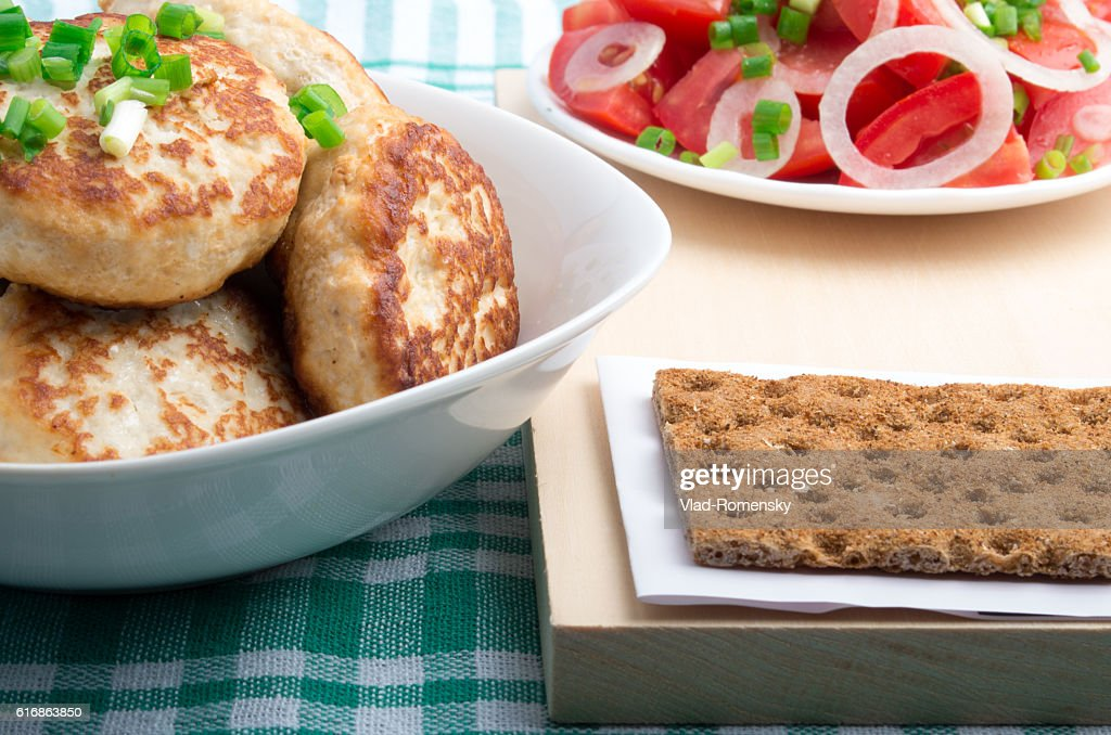 Chicken cutlets, salad of fresh tomatoes and rye biscuit : Stock Photo