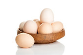 chicken eggs in a wooden plate isolated over white background