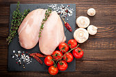 Chicken for grilled, spices, herbs,  tomatoes, mushrooms on dark background, top view. Raw meat chicken for cooking. Delicious balanced food concept