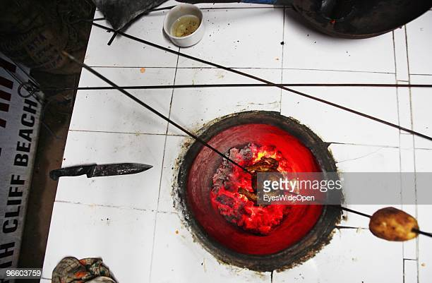A chicken gets cooked in a traditional tandoori oven with charcoal in Varkala on January 09 2010 in Varkala near Trivandrum Kerala India