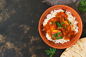 Chicken korma with a spicy sauce over white rice.Traditional Indian dish on a rustic background. Top view, copy space
