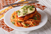 Chicken Parmigiana and pasta with tomatoes close-up on a plate on the table. horizontal