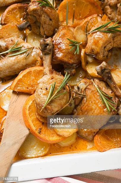 Chicken pieces with oranges and rosemary on baking tray