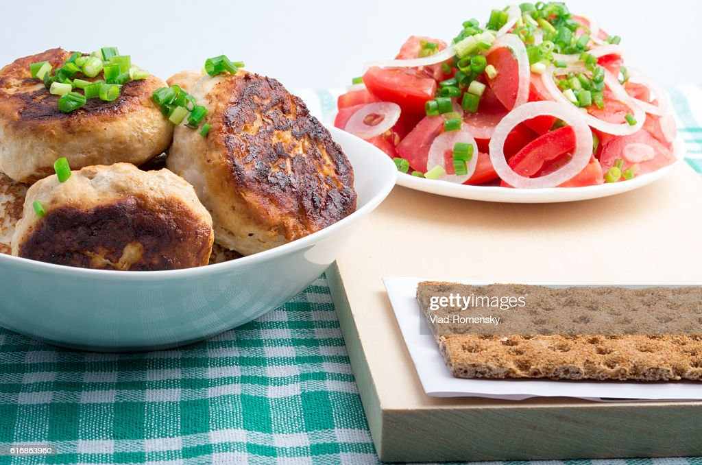 Chicken rissole, salad of fresh tomatoes and rye hardtack : Stock Photo