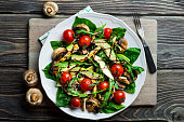 Chicken salad with avocado, tomatoes cherry, mushrooms and spinach