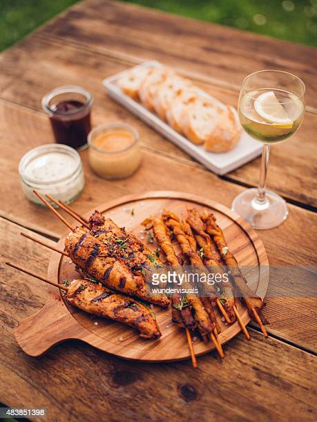 Chicken skewers and bacon twists on a wooden board