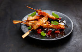 Chicken skewers with sweet-and-sour sauce and chili on plate