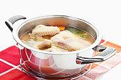 Chicken soup in stew pot on napkin