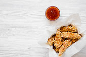 Chicken strips in paper box with sweet chili sauce on a white wooden table, view from above. Flat lay, top view, overhead. Copy space.