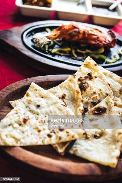 Chicken tandoori on a cast iron plate with naan bread and chutney. North Indian food