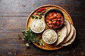 Chicken tikka masala spicy curry meat food in cast iron pot with rice and naan bread on wooden background