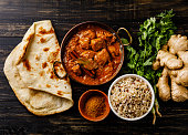 Chicken tikka masala spicy curry meat food with rice and naan bread on wooden background