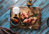 Chicken wings in cranberry sauce served on a wooden board with a glass of light beer, top view