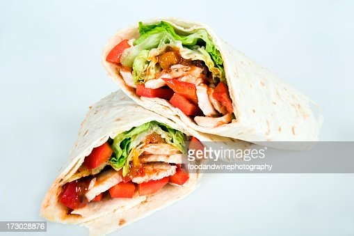 Chicken wrap cut in half on a white background