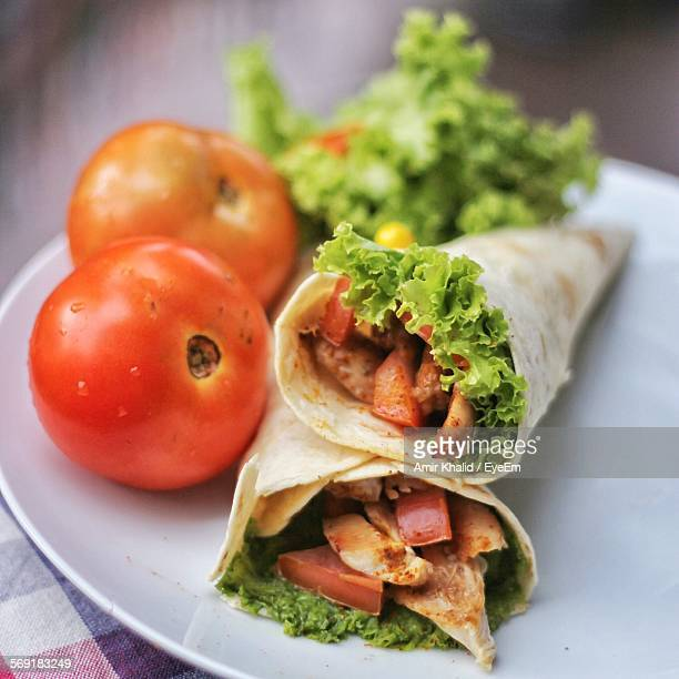 Chicken wrap with tomatoes and leaf on plate