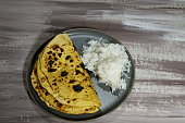 A vegetarian gluten free chickpea flour flat bread, rice and onions on wooden background.