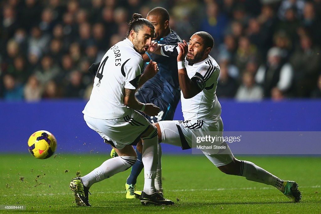 Chico Flores and Ashley Williams of Swansea City block a shot from Loic Remy of Newcastle United during the Barclays Premier League match between...