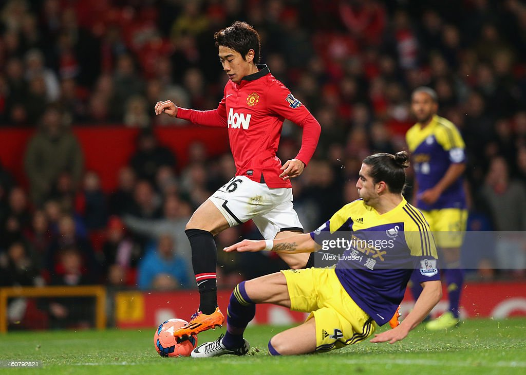 Chico Flores of Swansea City challenges Shinji Kagawa of Manchester United during the FA Cup with Budweiser Third round match between Manchester...