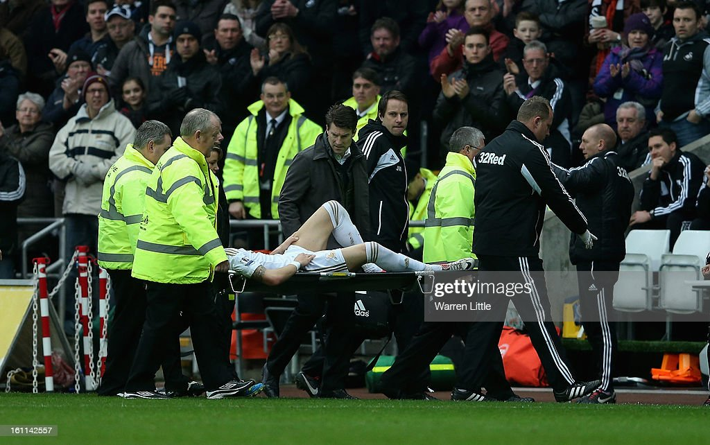 Chico Flores of Swansea City leaves the pitch injured as his manager Michael Laudrup looks on during the Premier League match between Swansea City and Queens Park Rangers at Liberty Stadium on February 9, 2013 in Swansea, Wales.