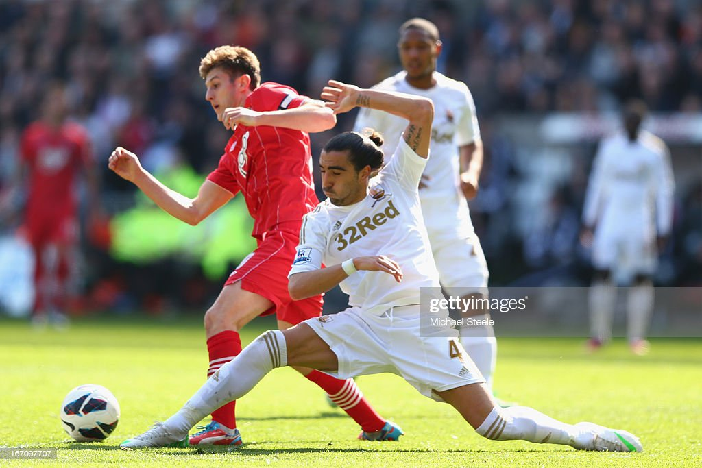 Chico Flores (R) of Swansea City tackles <a gi-track='captionPersonalityLinkClicked' href=/galleries/search?phrase=Adam+Lallana&family=editorial&specificpeople=5475862 ng-click='$event.stopPropagation()'>Adam Lallana</a> (L) of Southampton during the Barclays Premier League match between Swansea City and Southampton at the Liberty Stadium on April 20, 2013 in Swansea, Wales.