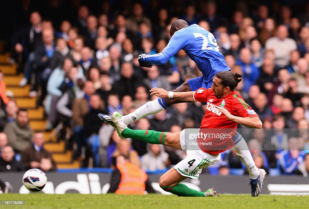 Chico Flores of Swansea City tackles Demba Ba of Chelsea during the Barclays Premier League match between Chelsea and Swansea City at Stamford Bridge...