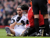 Chico Flores sits on the pitch following a challenge by West Ham United's English striker Andy Carroll during the English Premier League football...