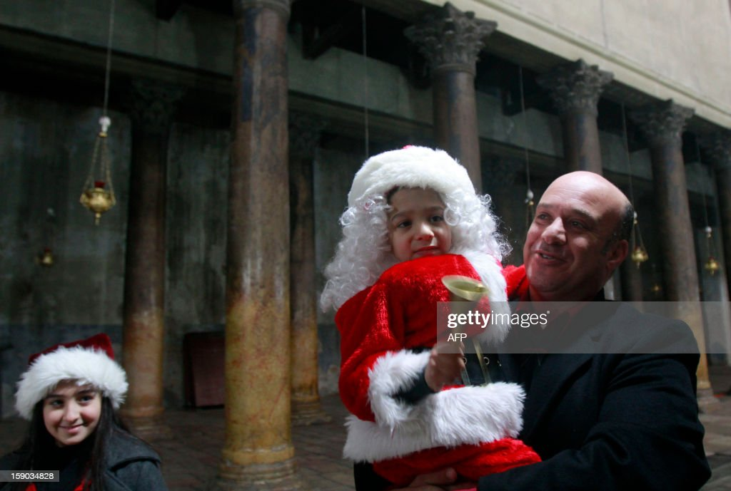 A chid dressed up as Santa Claus is carried through the central nave of the Church of the Nativity, accepted by Christians as the birth place of Jesus Christ, as faithful flock to the church to celebrate Christian Orthodox Christmas eve, on January 6, 2013, in the West bank town of Bethlehem.