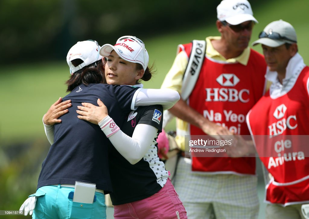 Chie Arimura of Japan (second from left) embraces <a gi-track='captionPersonalityLinkClicked' href=/galleries/search?phrase=Na+Yeon+Choi&family=editorial&specificpeople=4979078 ng-click='$event.stopPropagation()'>Na Yeon Choi</a> of South Korea on the 18th hole as their caddies look on during the second round of the HSBC Women's Champions at the Tanah Merah Country Club on February 25, 2011 in Singapore.