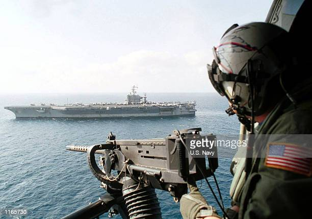 Chief Aviation Warfare Systems Operator scans the horizon above USS Carl Vinson from behind his GAU16 50 caliber machine gun aboard an SH60H...
