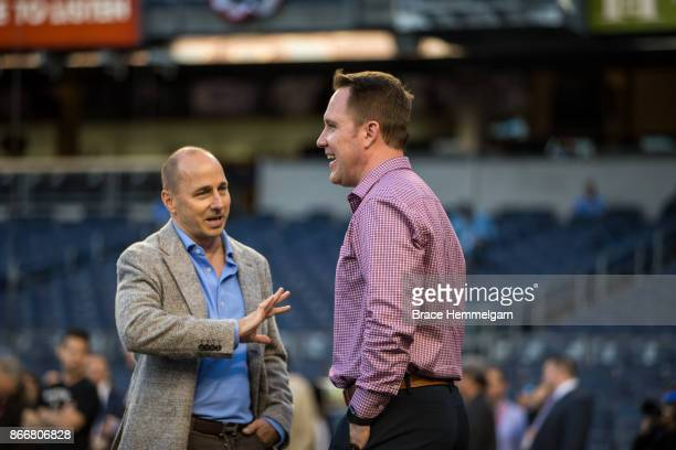 Chief baseball officer Derek Falvey of the Minnesota Twins talks with New York Yankees general manager Brian Cashman prior to the American League...
