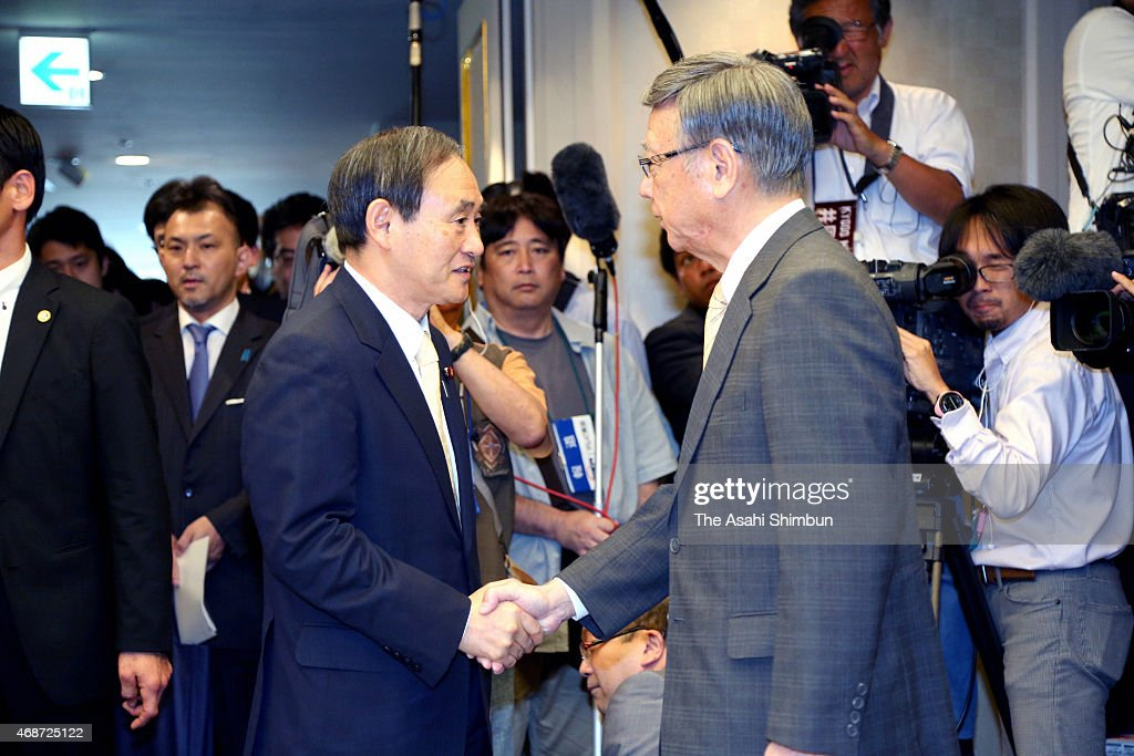 Chief Cabinet Secretary <a gi-track='captionPersonalityLinkClicked' href=/galleries/search?phrase=Yoshihide+Suga&family=editorial&specificpeople=3868279 ng-click='$event.stopPropagation()'>Yoshihide Suga</a> (L) and Okinawa Governor <a gi-track='captionPersonalityLinkClicked' href=/galleries/search?phrase=Takeshi+Onaga&family=editorial&specificpeople=9971702 ng-click='$event.stopPropagation()'>Takeshi Onaga</a> (R) shake hands before the start of their meeting on April 5, 2015 in Naha, Okinawa, Japan. In his long-awaited first talks with a key Cabinet member, Okinawa Governor <a gi-track='captionPersonalityLinkClicked' href=/galleries/search?phrase=Takeshi+Onaga&family=editorial&specificpeople=9971702 ng-click='$event.stopPropagation()'>Takeshi Onaga</a> reaffirmed his defiant stance that it is 'absolutely impossible' to relocate a U.S. Marine Corps base within the prefecture.