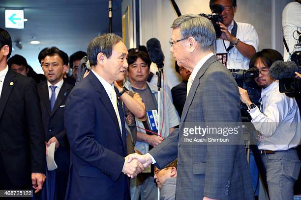 Chief Cabinet Secretary Yoshihide Suga and Okinawa Governor Takeshi Onaga shake hands before the start of their meeting on April 5 2015 in Naha...