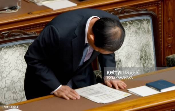 Chief Cabinet Secretary Yoshihide Suga bows when the upper house of parliament passes a bill that allows Emperor Akihito to step down during the...