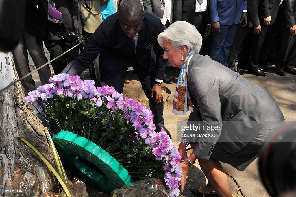 IMF chief Christine Lagarde (C) visiting the Ivory Coast lays a wreath on January 7, 2013 at the foot of a tree in the Abidjan street where 63 died in a stampede after a firework display, part of the New Year celebrations. AFP PHOTO / ISSOUF SANOGO