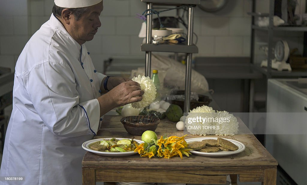 Chief Don Chon serves a plate of ant eggs and chrysantemums and mosquito eggs with nopal (cactus leaves) with pumpkin flowers (L) in his restaurant's kitchen on August 18, 2013 . The Restaurant Bar Don Chon, in downtown Mexico City, was founded in 1924 specializes in exotic Mexican food.
