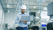 Chief Engineer in the Hard Hat Walks Through Light Modern Factory While Holding Laptop. Successful, Handsome Man in Modern Industrial Environment.