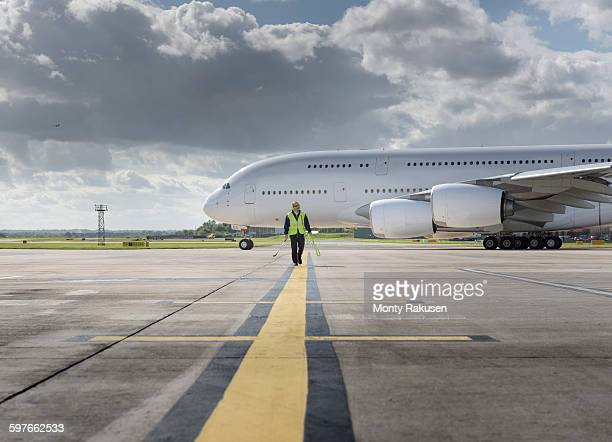 Chief engineer walking from runway as A380 aircraft departs from airport