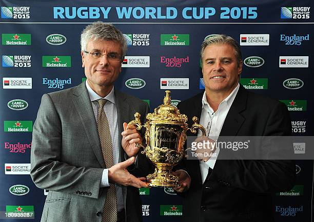 Chief Executive Brett Gosper and Partner of Clifford Chance Daniel Sandelson pose for photos with The Webb Ellis Cup during the Rugby World Cup press...