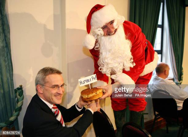 Chief Executive of Ryanair Michael O'Leary gives a Christmas bun labelled 'Humble Pie' to Vincent Wall of Dublin Airport Authority during a press...