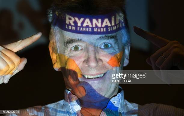 Chief Executive Officer of Irish airline Ryanair Michael O'Leary poses with his company's logo projected on his face as he attends a press conference...