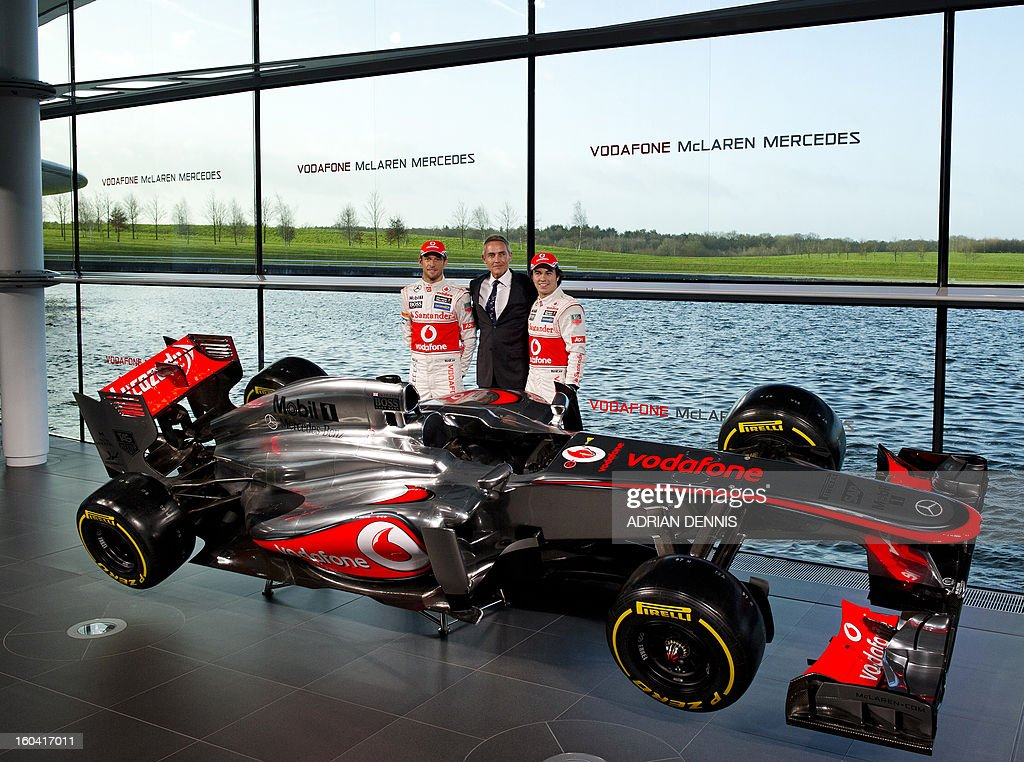 Chief Executive Officer of McLaren Group and Team Principal Martin Whitmarsh (C) poses for pictures with Mexican F1 driver Sergio Checo Perez (R) and British F1 driver Jenson Button (L) as the new McLaren Mercedes MP4-28 F1 racing car for the 2013 season is unveiled at the McLaren Technology Centre in Woking, southern England, on January 31, 2013. Mexican driver Sergio Checo Perez joins Britain's Jenson Button for the 2013 season following the departure of Britain's Lewis Hamilton.