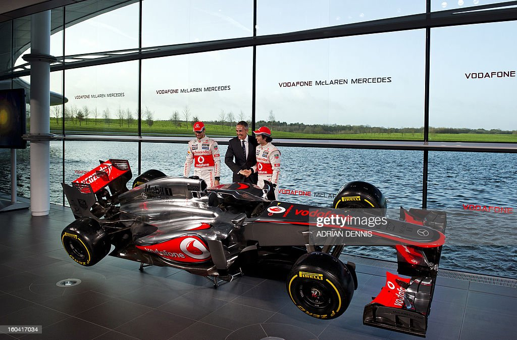 Chief Executive Officer of McLaren Group and Team Principal Martin Whitmarsh (C) shakes hands with Mexican F1 driver Sergio Perez (R) as British F1 driver Jenson Button (L) looks on as the new McLaren Mercedes MP4-28 F1 racing car for the 2013 season is unveiled at the McLaren Technology Centre in Woking, southern England, on January 31, 2013. Mexican driver Sergio Checo Perez joins Britain's Jenson Button for the 2013 season following the departure of Britain's Lewis Hamilton.