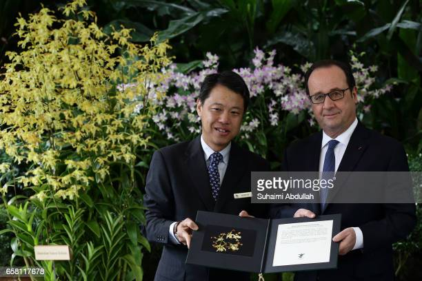 Chief Executive Officer of National Parks Board Kenneth Er and French President Francois Hollande pose for a photo with the orchid 'Dendrobium...