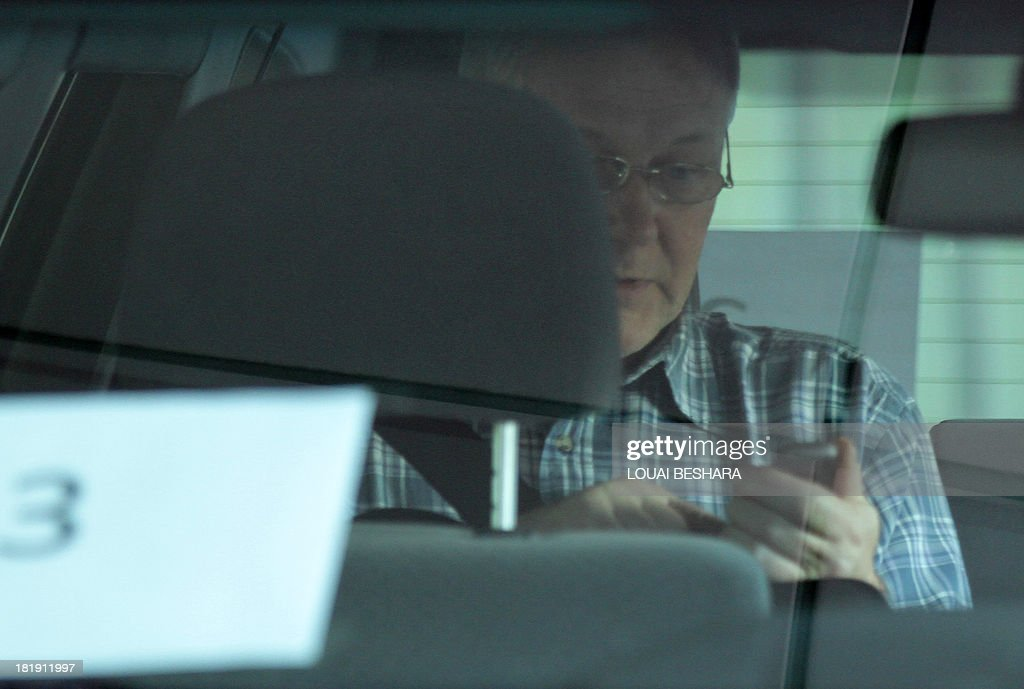Chief expert, Ake Sellstrom checks his mobile phone in a vehicle as UN chemical weapons experts' convoy leaves an hotel in the Syrian capital Damascus on September 26, 2013. The experts arrived in Syria on September 25 on their second mission to the country, where they will examine some 14 alleged incidents involving the use of chemical weapons.
