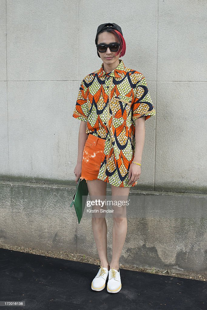 Chief fashion editor of Men's Health China Boynam wears a Marc Jacobs hat, Koops sunglasses, Vintage Kenzo shirt, Levi's shorts, Givenchy clutch and Churches shoes on day 4 of Paris Collections: Men on June 29, 2013 in Paris, France.