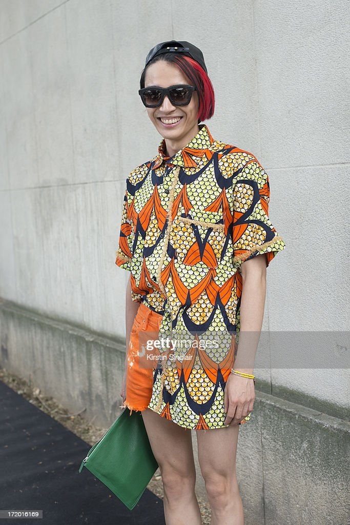 Chief fashion editor of Men's Health China Boynam wears a Marc Jacobs hat, Koops sunglasses, Vintage Kenzo shirt, Levi's shorts, Givenchy clutch on day 4 of Paris Collections: Men on June 29, 2013 in Paris, France.