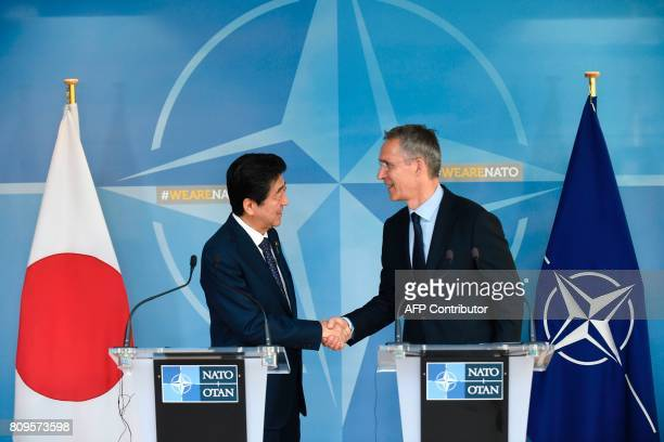 NATO chief Jens Stoltenberg and Japanese Prime Minister Shinzo Abe shake hands during a press conference at the NATO headquarters in Brussels on July...